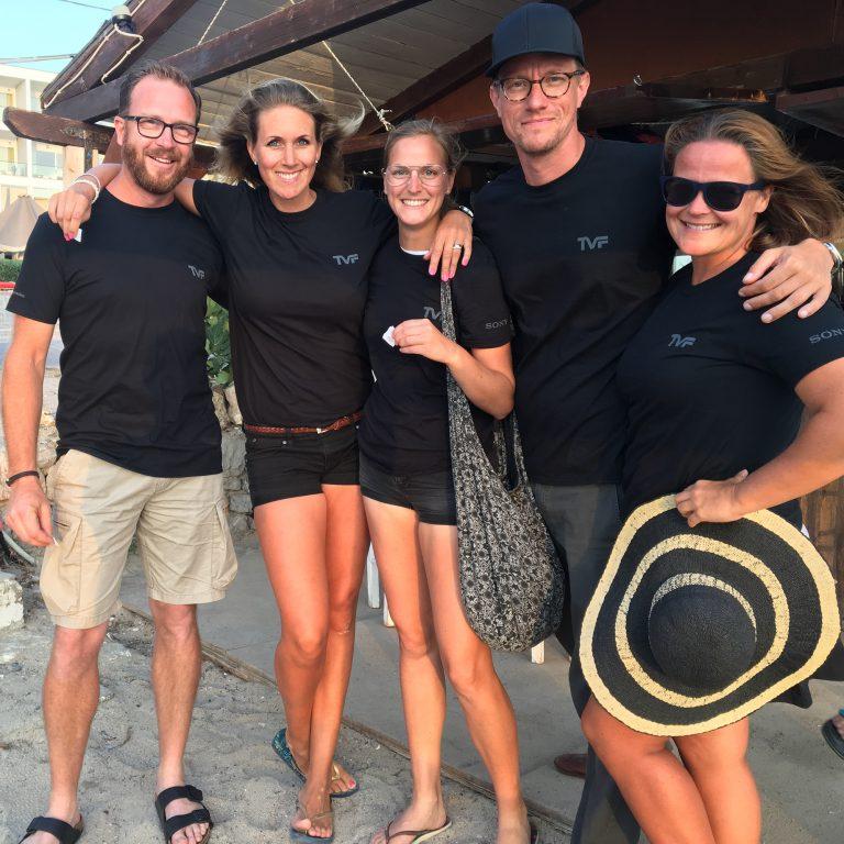 Fem glada fotografer i tvf-tröjor poserar framför kameran