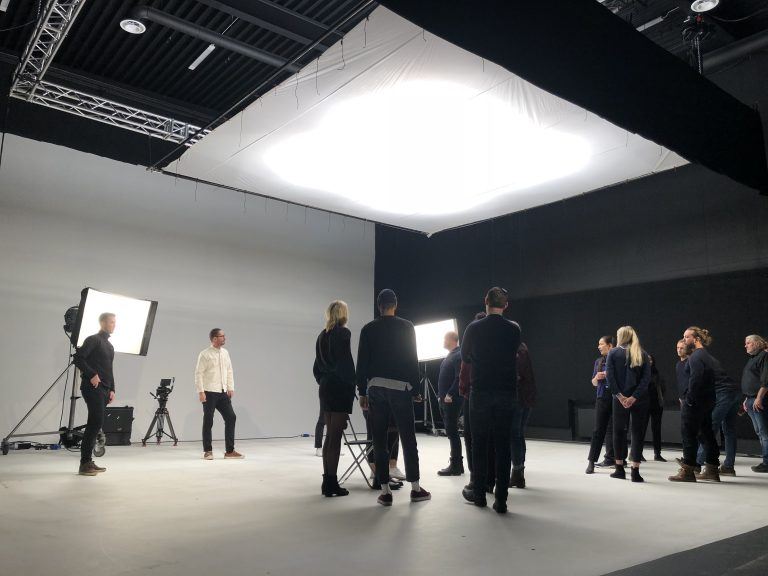 Personer i tv-studio med lampor och kameror