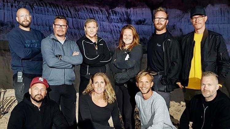 Gruppfoto med tio fotografer i en mörk utomhusmiljö